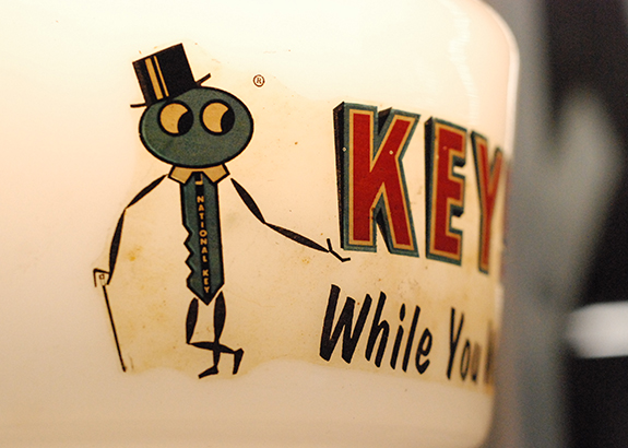 An coffee mug with a key depicting to have a top hat and cane from Annie's Dependable Service Hardware in Washington D.C.